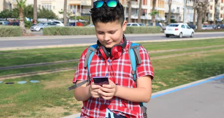 desviando o olhar : Portrait of a happy cute teenager boy making selfie at the city park