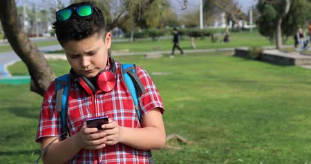 boyhood : Portrait of a happy preteen boy at the green spring park talking on smartphone  Technology, internet communication and people concept, Smartphone addiction