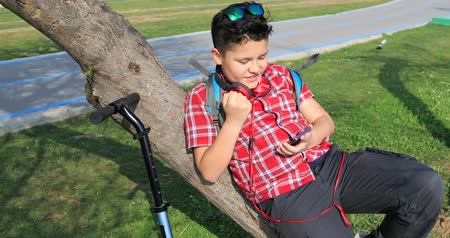 fiatalos : Young school boy  using smartphone and relaxing at the city park Stock mozgókép