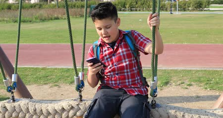 fiatalos : Portrait of a happy preteen boy using smartphone and swinging at the playground. Technology, internet communication and people concept, Smartphone addiction Stock mozgókép