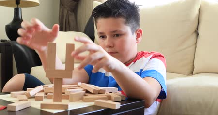 quebra cabeças : Preteen boy  playing with wooden tower block game  at home Vídeos