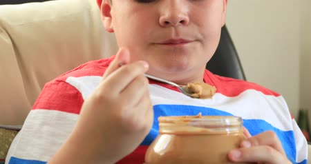 cukorbaj : Portrait Of A Child Sitting On A Sofa With Spoon  Eating Peanut Butter From Jar