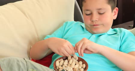 walnut shell : Portrait of a young preteen boy lying on sofa watching television and eating healthy snack
