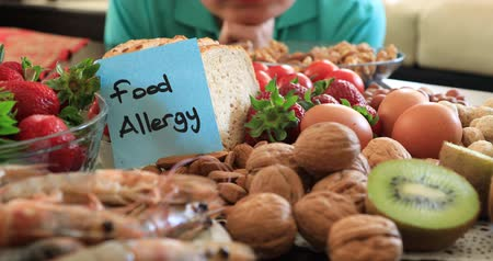 arenque : Portrait of sad young boy with food allergy looking at the allergic food. Peple food and health care concepts. Vídeos