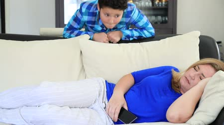thieve : Young gamer boy filching mothers smart phone, when she sleeping on sofa at home Stock Footage