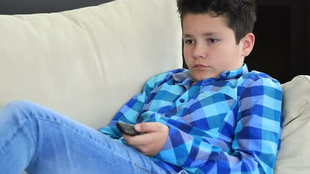 watch tv : Portrait of a young preteen boy with remote controller  lying on sofa watching television at home