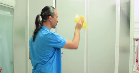obsessive : Man cleaning shower cubicle window Stock Footage