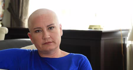 rak : Middle aged sick, bald woman with cemotheraphy patient looking at the camera.Breast cancer survivor Wideo