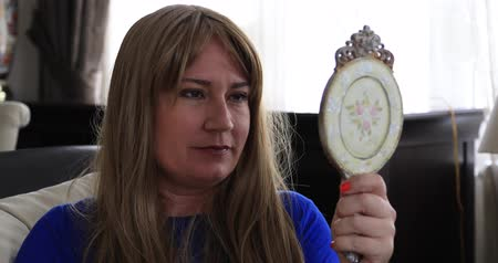 seno scoperto : Middle aged depressed sick woman with breast cancer looking at the mirror. Take out her wig, Breast cancer survivor
