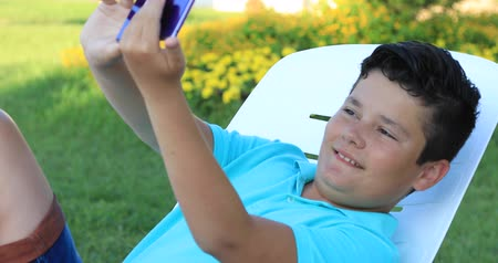 scolari : Portrait of a happy cute teenager boy making selfie at the outdoor Filmati Stock