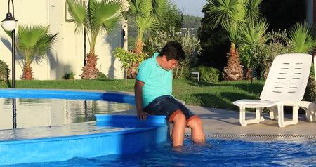 yüzme havuzu : Portrait of a cute teenage boy sitting at the edge of a swimming pool and relaxing on a sunny summer day Stok Video