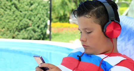 fiatalos : Portrait of a cute teenage boy with headphone sitting on a sunbed near the swimming pool and using smartphone on a sunny summer day. Technology, internet communication and people concept, smartphone addiction