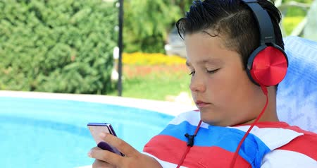 выражающий : Portrait of a cute teenage boy with headphone sitting on a sunbed near the swimming pool and using smartphone on a sunny summer day. Technology, internet communication and people concept, smartphone addiction