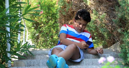 boyhood : Preteen boy with smartphone texting message or playing game at the nature. Technology, internet communication and people concept. Smartphone addiction