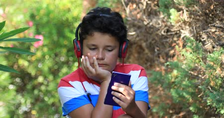školák : Preteen boy with smartphone texting message or playing game at the nature. Technology, internet communication and people concept. Smartphone addiction