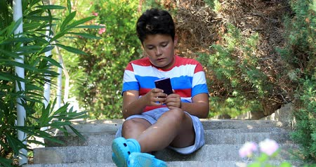 fiatalos : Preteen boy with smartphone texting message or playing game at the nature. Technology, internet communication and people concept Stock mozgókép