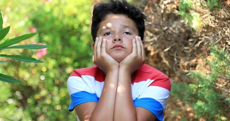 houding : Portrait of a unhappy preteen boy sitting at the park and looking very sad Stockvideo