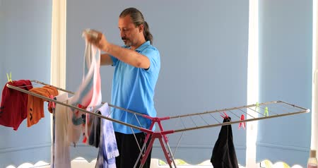 prát : Man hanging clothes on a rack dryer