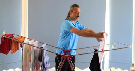 сушка : Man hanging clothes on a rack dryer