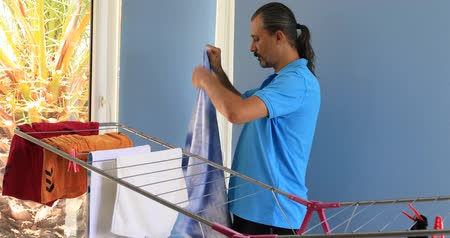 varal : Man hanging clothes on a rack dryer