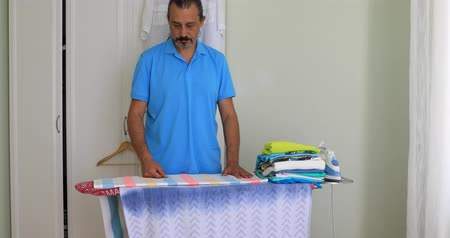 гладильный : Middle Aged  Man Ironing Clothes With Electric Iron