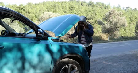 hayal kırıklığına uğramış : Portrait of a troubled woman  talking by smartphone near broken car with open hood Stok Video