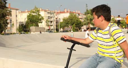 lonely : Handsome unhappy preteen boy with scooter sitting alone at the skateboard park