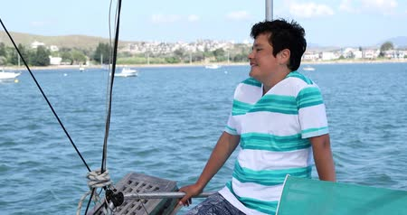 моряк : Portrait of a handsome cute teenager traveler  looking around and smiling on yacht deck at summer vacation Стоковые видеозаписи