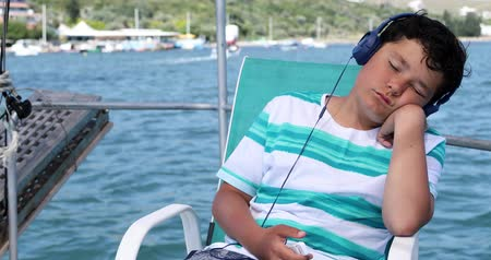 voyager : Handsome preteen boy with headphone listening to music,  relaxing and sleeping on yacht deck at summer vacation Stock Footage