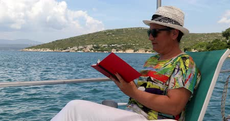 voyager : Portrait of a relaxed, happy middle aged woman sitting luxury yacht deck travelling and reding a novel at summer vacation Stock Footage
