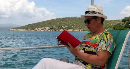 descontraído : Portrait of a relaxed middle aged woman sitting luxury yacht deck travelling and reding a novel at summer vacation