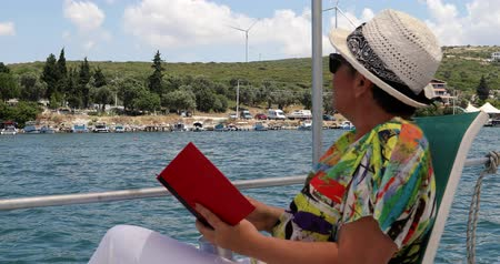 voyager : Portrait of a relaxed middle aged woman sitting luxury yacht deck travelling and reding a novel at summer vacation
