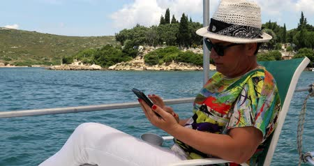 boat tour : Portrait of a middle aged beautiful woman is sitting on the deck of a yacht with a smartphone at summer vacation Stock Footage