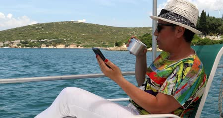 voyager : Portrait of a middle aged beautiful woman is sitting on the deck of a yacht with a smartphone at summer vacation Stock Footage