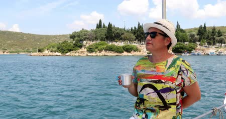 voyager : Portrait of a caucasian female tourist woman in glasses  on luxury sailing boat relaxing and looking around at summer vacation