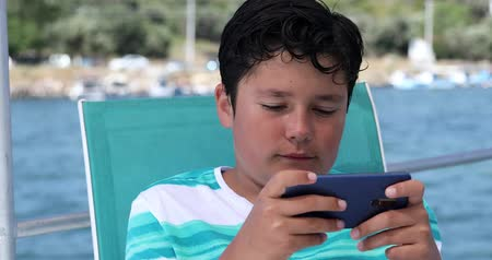 curto : Happy teenager gaming with smart phone on yacht deck at summer vacation Stock Footage