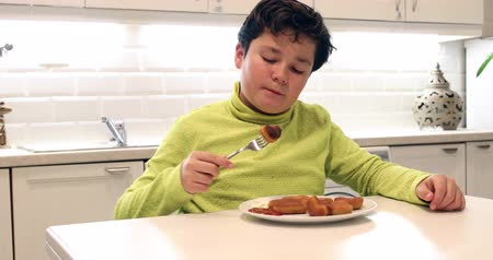 nibble : Portrait of a young boy eating chicken nuggets and looking at the camera  in the kitchen