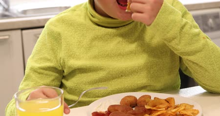 školák : Portrait of a young boy eating chicken nuggets and potato chips in the kitchen