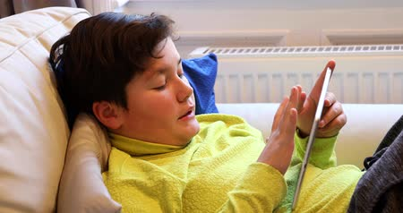 kifejező pozitivitás : Portrait of a relaxed preteen boy laying sofa with digital tablet texting message or playing game at home. Technology, internet communication and people concept, Smartphone addiction