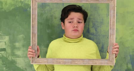 piada : Portrait of a handsome young boy  looking through emty frame and making silly faces to a camera