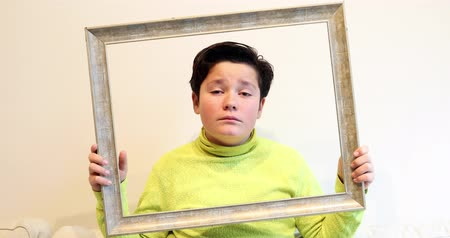 felkiáltás : Portrait of a handsome young boy  looking through emty frame and making silly faces to a camera