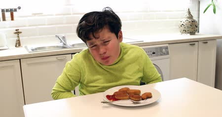 hasi : Painful preteen boy having abdominal pain, eating too much fried food in the kitchen