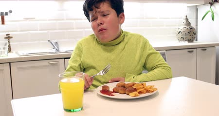 frying : Painful preteen boy having abdominal pain, eating too much fried food in the kitchen