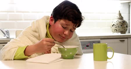 puericultura : Portrait of a sick young boy with flu eating hot chicken soup in kitchen
