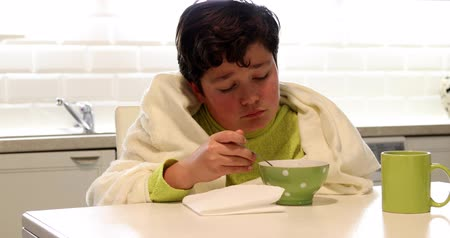 examinar : Portrait of a sick young boy with flu eating hot chicken soup in kitchen