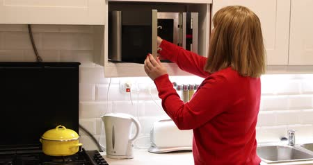 mikrohullámú : Woman in kitchen using microwave oven