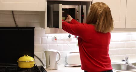 microonda : Woman in kitchen using microwave oven