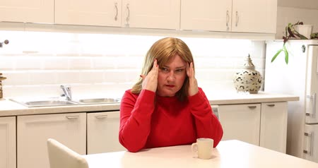 adversidade : Portrait of a middle aged woman suffering a migraine at home alone Stock Footage