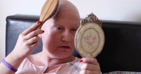 obsession : Mentally ill woman with bald head looking at the mirror and brushing her hair