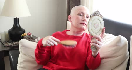 aflição : Mentally ill woman with bald head looking at the mirror and brushing her hair